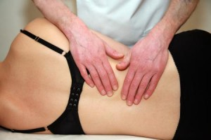 Gilly Arbuckle Osteopath treating a woman's upper back pain